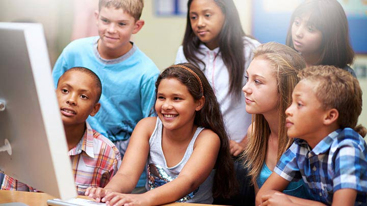 Smiling 3rd grade students start a video conference in the classroom