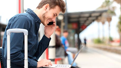 Man on train platform participates in free webinar from laptop and mobile app