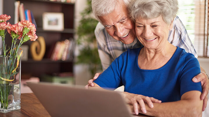 Elderly couple using a laptop in the confort of their house
