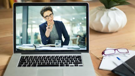 A laptop plays a video recording of a business woman