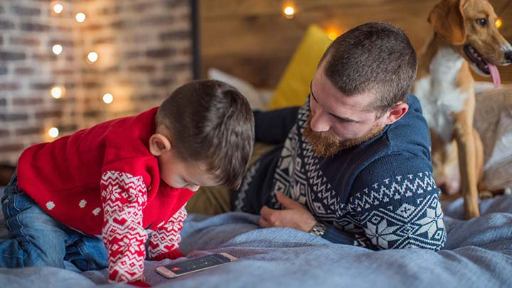 Father, son and pet dog sitting on bed with mobile phone to call Santa's Hotline with Christmas lights in background