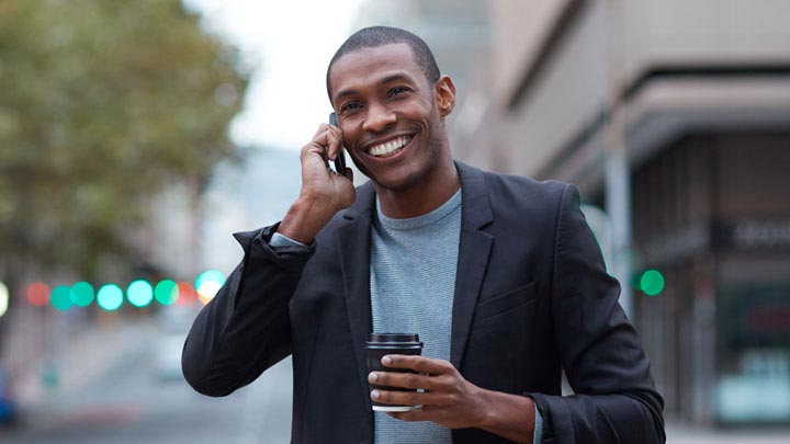 Man smiling on the phone walking on the street